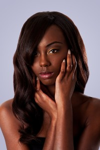 Woman with wavy extensions holding her face